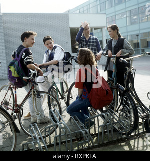 1980s - 1990s Youth : Teenagers on school yard chatting outside near bicycle parking rack after school time, on - Stock Photo