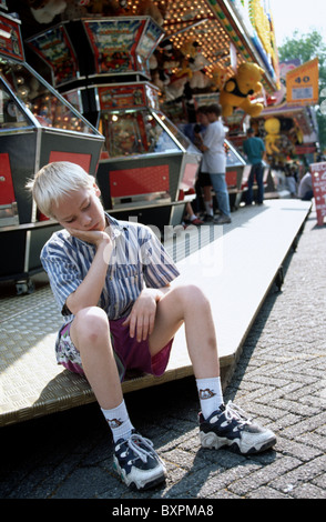 Sulky looking boy sit at fairground attraction - Stock Photo