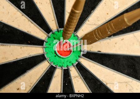 Two darts in a bullseye on a dartboard - Stock Photo