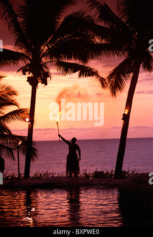 Native In A Grass Skirt Holding A Flaming Torch By Coast At Sunset - Stock Photo
