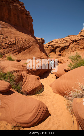 Man hiking through navajo Waterholes Canyon in the desert near Page in Arizona USA on a hot sunny summer day - Stock Photo