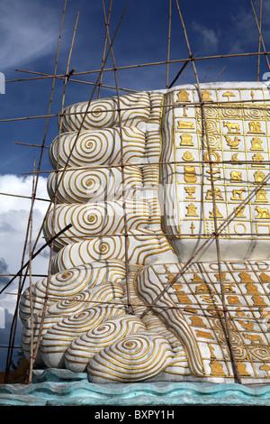 The Mya Tha Lyaung Reclining Buddha being restored using bamboo scaffolding in Bago, Myanmar. (Burma) - Stock Photo
