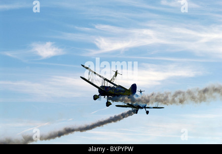Two stunt biplanes with two wing-walking stunt performers (both girls) at an airshow. - Stock Photo
