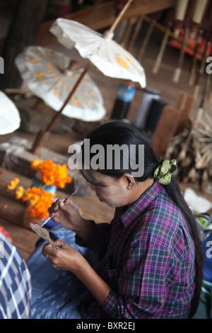 A local Intha lady creating paper umbrellas on Inle Lake, Shan State, Mayanmar (Burma) - Stock Photo