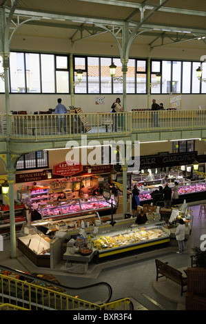 Diary & meat produce stalls in a French covered market shop an overview of trader and customer Town centre Les Sables - Stock Photo