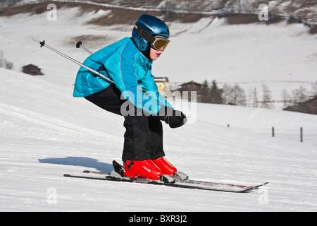 Child wearing a ski helmet skiing fast downhill on snow ski slopes in the Austrian Alps. Rauris Austria Europe. - Stock Photo