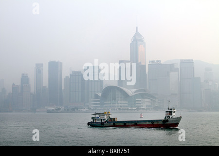 Boat in Hong Kong harbour against the skyline in Hong Kong, China - Stock Photo