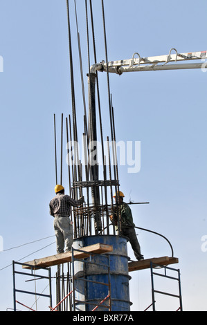 Workers pouring concrete in support post at construction site, Puerto Penasco, Sonora, Mexico - Stock Photo