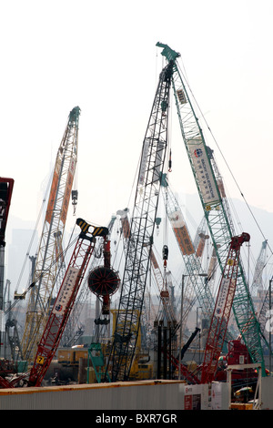 Cranes on a building and construction site in Kowloon in Hong Kong, China - Stock Photo