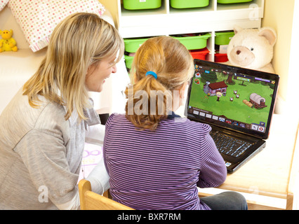 teacher helping young girl to use a computer, playing a computer game - Stock Photo