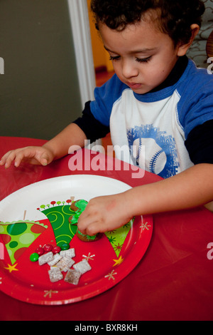 Three-year-old Mexican American boy decorated a gingerbread cookie at the kitchen table - Stock Photo