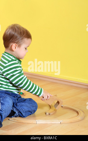 Cute caucasian toddler playing with toy train in kindergarten. Extra text space on upper right corner. - Stock Photo