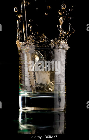 Glass of whisky on a black background. Whisky splash in a glass. Whisky with ice. - Stock Photo