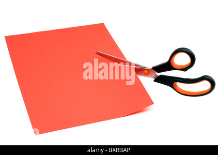Scissors cutting through a sheet of red A4 paper - Stock Photo