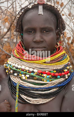 Nyangatom (Bumi) woman with piles of beads in her village, Omo river Valley, Ethiopia Africa - Stock Photo