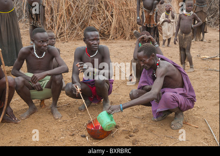 Nyangatom (Bumi) men sharing a calabash of cow blood, Omo river valley, Ethiopia Africa - Stock Photo