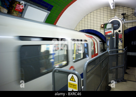 A tube train leaving Piccadilly Underground Station, London, England, UK - Stock Photo