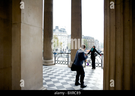 A young man photographing his girlfriend in the entranceway to the National Gallery, Trafalgar Square, London, England, - Stock Photo