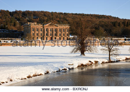 Chatsworth House stately home and River Derwent on snow covered country estate. Chatsworth Park, Derbyshire, England, - Stock Photo