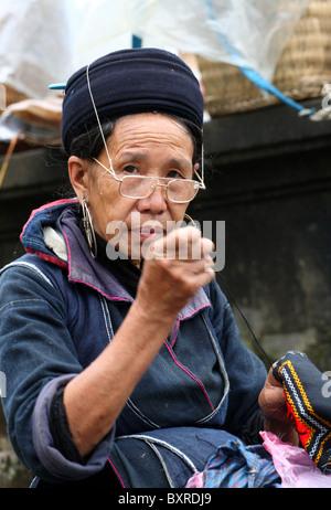 Black Hmong hill tribe ethnic minority sewing garments in Sapa, north Vietnam - Stock Photo