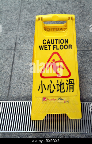 Chinese caution wet floor warning sign in Hong Kong, China - Stock Photo
