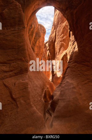 HDR image of arch and hole in the eroded, narrow, red sandstone confines of Peekaboo Canyon - Stock Photo