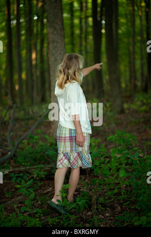 Young woman in woods pointing her finger into the distance - Stock Photo