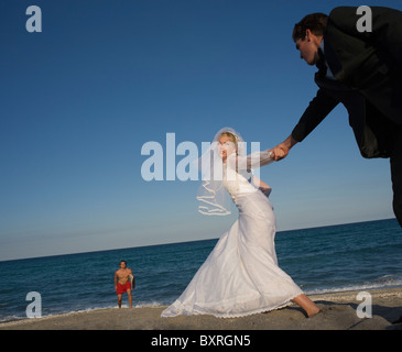 Bride and groom holding hands on beach, lifeguard in background - Stock Photo