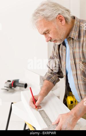 Home improvement - handyman measure porous brick in workshop - Stock Photo