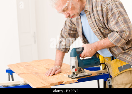 Home improvement - handyman cut wood with jigsaw in workshop - Stock Photo