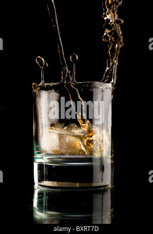 Glass of whiskey on a black background. Whiskey splash in a glass. Whiskey with ice. - Stock Photo