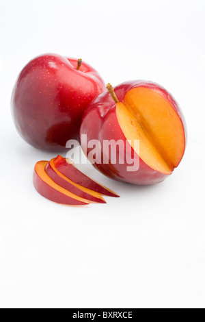Sliced plum and whole on white background - Stock Photo