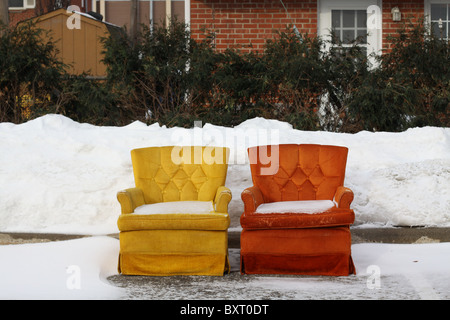 Two bright, colorful chairs sitting outside in the snow. - Stock Photo