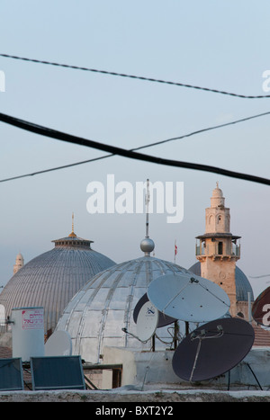 Jerusalem Old City. View of church domes and minarets with aerial dishes and cables. - Stock Photo