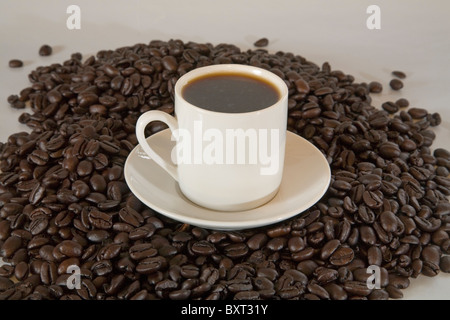 A cup of espresso on a pile of espresso coffee beans - Stock Photo
