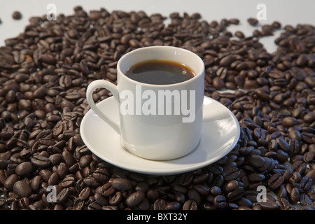 A cup of espresso with dark roast espresso beans - Stock Photo