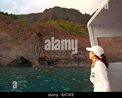 Photo of mature woman looking at waterfall on Kauai's Na Pali coastline, taken from the water in early morning light - Stock Photo