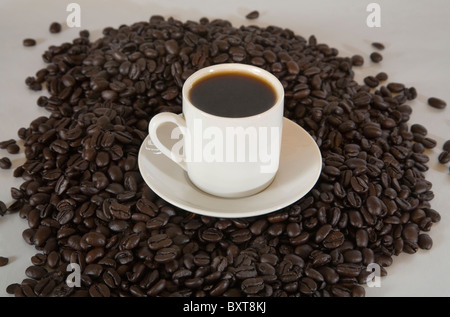 A cup of espresso coffee on a pile of espresso coffee beans - Stock Photo