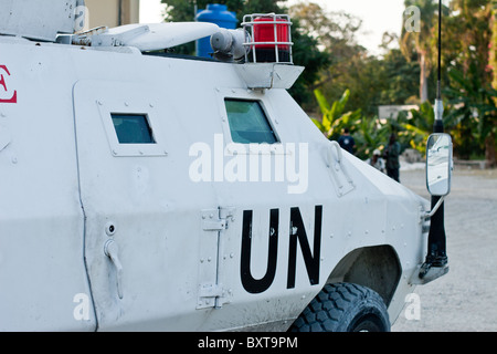 A United Nations vehicle and soldiers provide protection to a humanitarian aid agency distributing food in Haiti. - Stock Photo