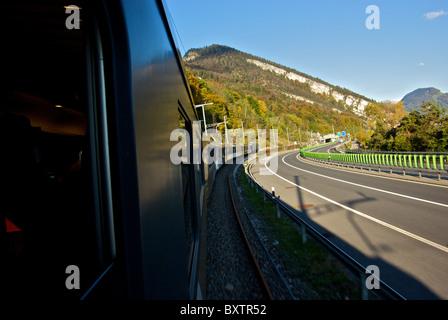 Golden Pass Express train highway landscape in motion blur coming into Luzern Switzerland beside motorway - Stock Photo