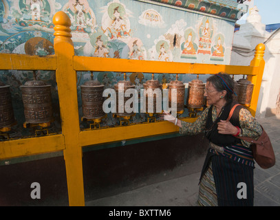 Tibetan pilgrim spins a prayer wheel at the Tibetan Buddhist stupa of Boudhanath in Kathmandu. - Stock Photo