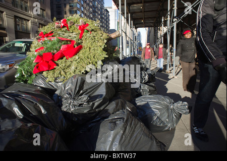 Bags of trash and a giant wreath await pick-up in the Chelsea neighborhood of New York - Stock Photo