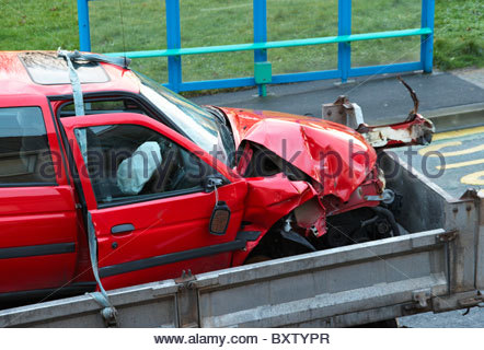 a damaged smashed red car that has been in a road accident on the back of a lorry trailer with deflated airbag - Stock Photo