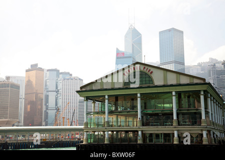 Central Pier, one of the star ferry terminal on Hong Kong Island with the iconic bank of China behind - Stock Photo