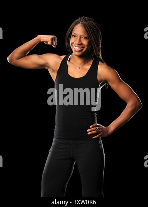 Young African American woman flexing biceps isolated over black background - Stock Photo