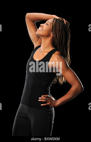 African American woman stretching isolated over black background - Stock Photo
