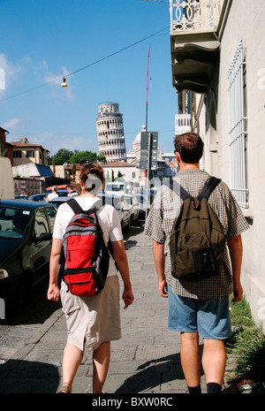 Tourists Walking Along Via Card. With Leaning Tower Of Pisa In The Distance - Stock Photo