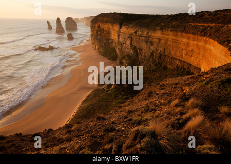 Australia Victoria Port Campbell National Park Setting sun over eroded cliffs along Tasman Sea at Twelve Apostles - Stock Photo