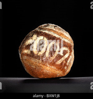 round loaf of bread dusted with a year date - Stock Photo