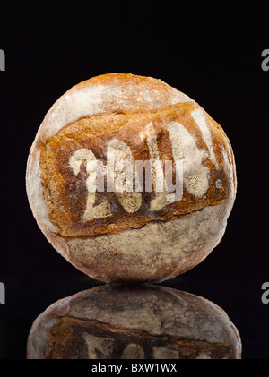 round loaf of bread dusted with the year date - Stock Photo